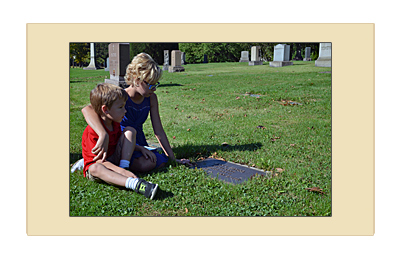 Children sitting on the grass in cemetery looking at their father's flat bronze veterans grave marker.